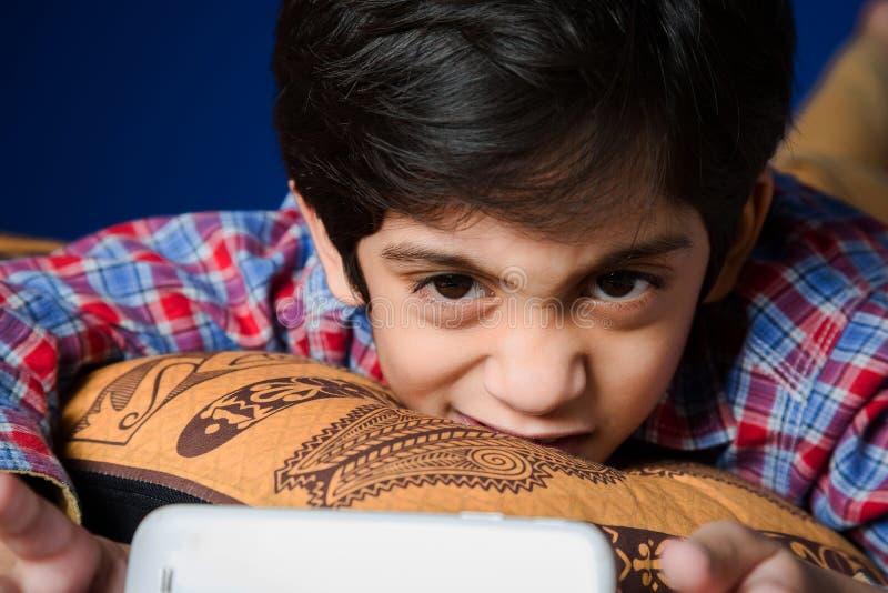 Enfant à l'aide d'un Smart-téléphone avec l'expression drôle photo libre de droits