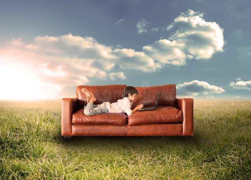 Enfant à l'aide de l'ordinateur portable sur le divan dans le domaine images libres de droits