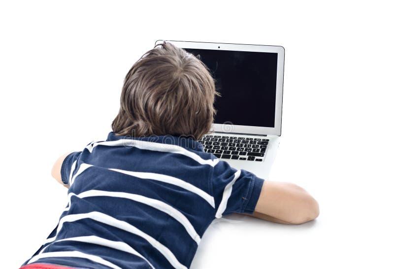 Enfant à l'aide de l'ordinateur portable sur le plancher image libre de droits
