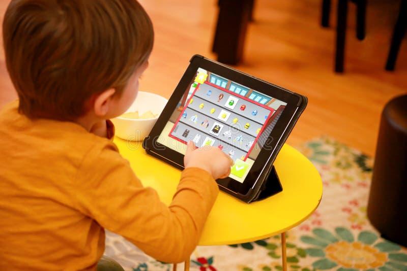 Enfant à l'aide du PC de comprimé sur le lit à la maison Le garçon mignon sur le sofa observe la bande dessinée, joue des jeux et photos stock