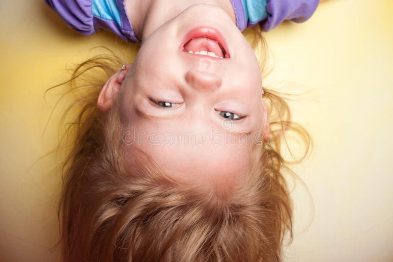 Enfant à l'envers sur le fond jaune photo libre de droits