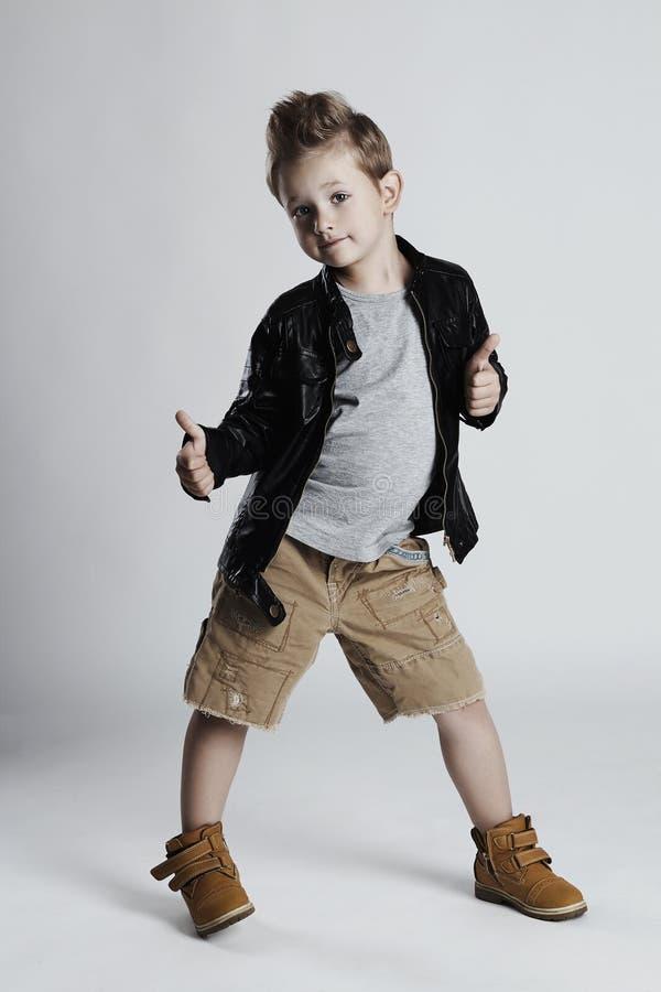 Enfant à la mode dans le manteau en cuir coiffure de petit garçon enfant de sourire drôle photographie stock libre de droits