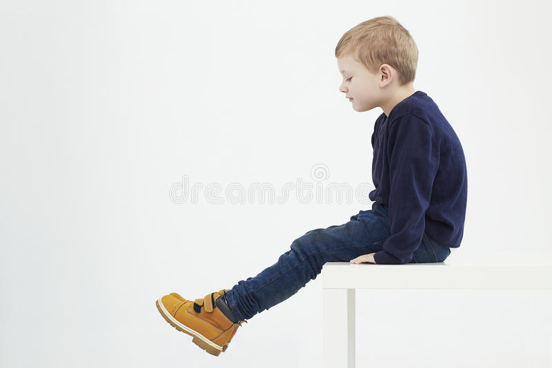 Enfant à la mode dans les bottes jaunes Enfants de mode petit garçon s'asseyant sur une table images stock