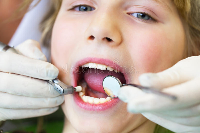 Enfant à la réception à la réception de dentiste au dentistClose vers le haut du portrait d'une petite fille de sourire au dentis photographie stock libre de droits