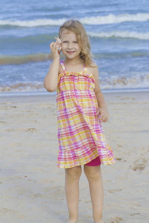 Enfant écoutant l'interpréteur de commandes interactif à la plage. photo libre de droits