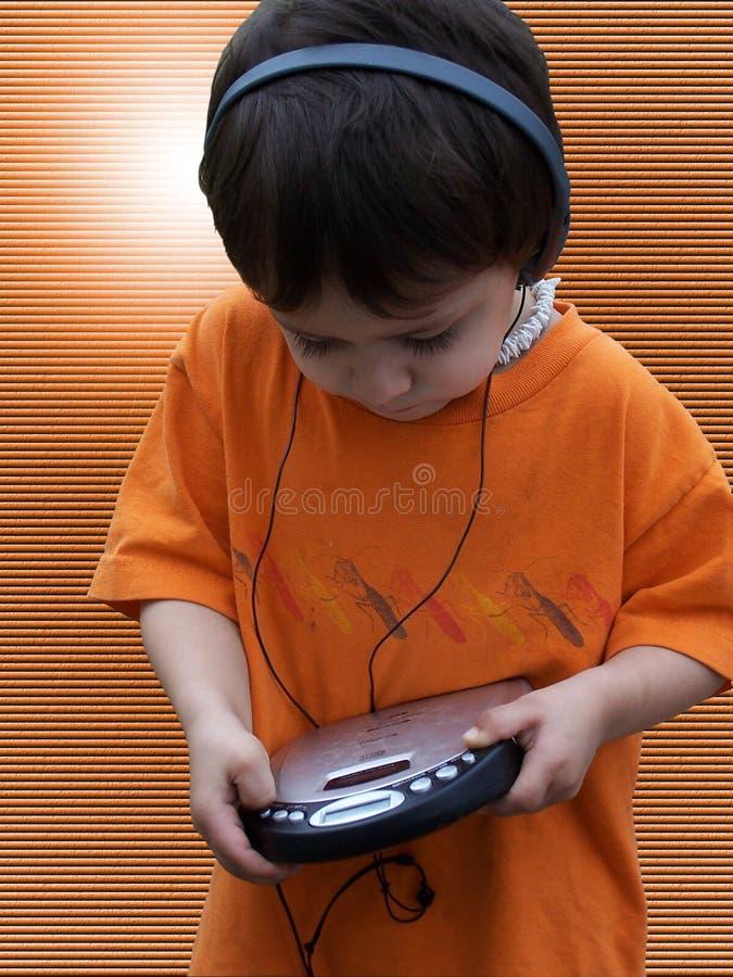 Enfant écoutant la musique - orange images stock