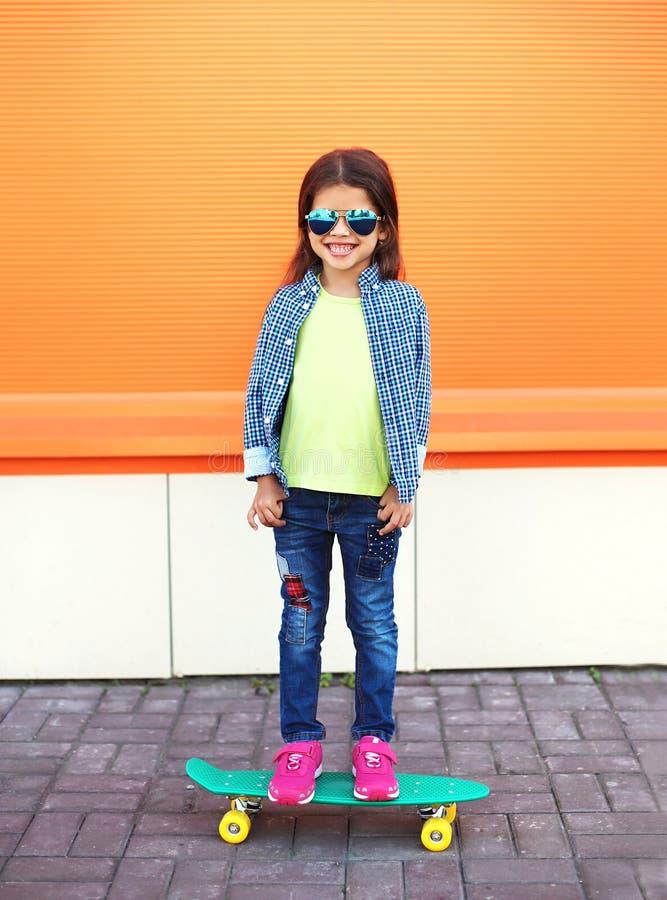 Enfant élégant de sourire gai heureux de petite fille avec la planche à roulettes photos libres de droits