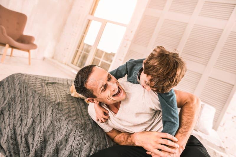 Enfant énergique jeu-luttant avec son papa sur le lit image stock