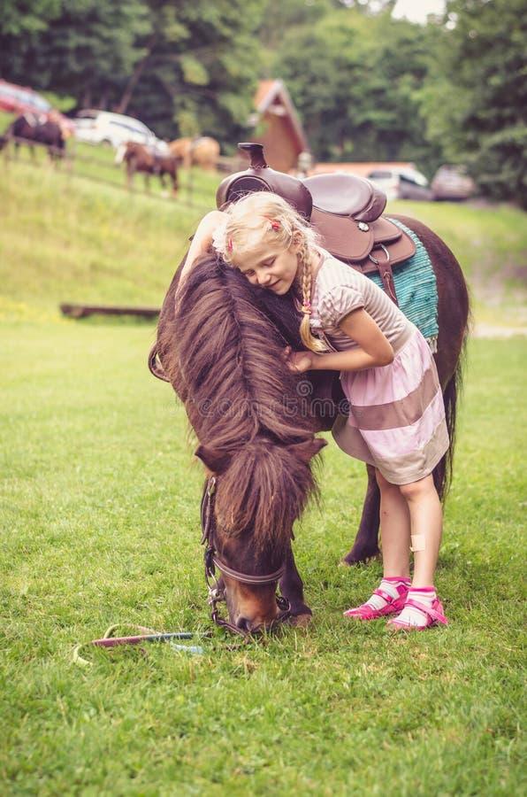 Enfant étreignant le petit poney brun images libres de droits