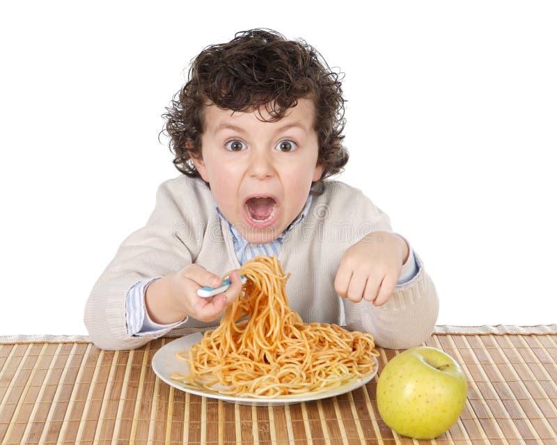 Enfant adorable affamé au moment de la consommation photo stock