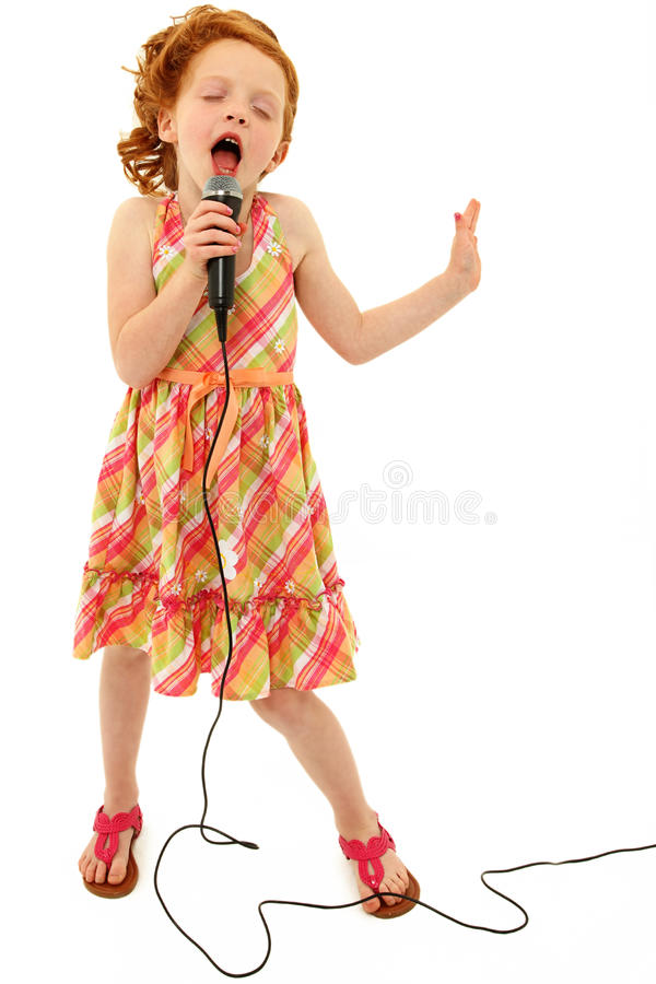 Enfant adorable chantant dans le microphone image stock