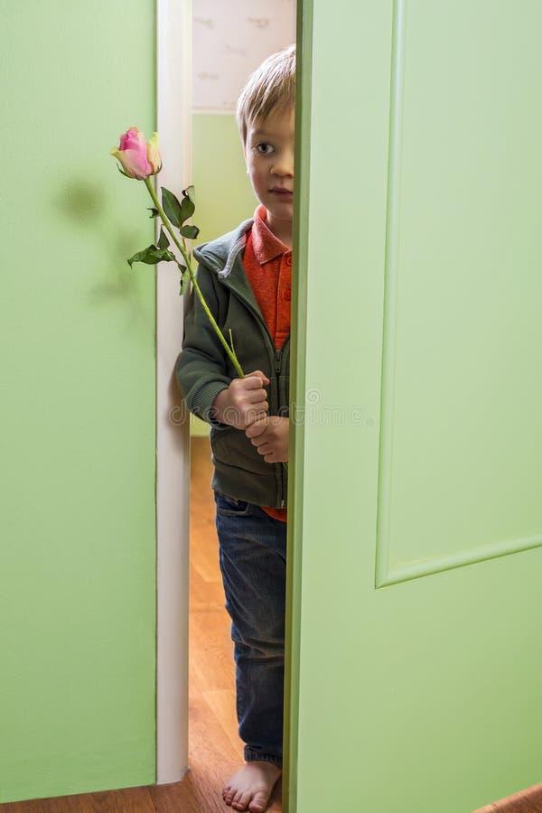 Enfant adorable tenant une rose images stock