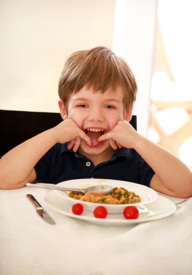 Enfant affam? s'asseyant dans la chaise ? la table dans la cuisine et mangeant avec la cuill?re des pois cuits avec la tomate Rep image stock