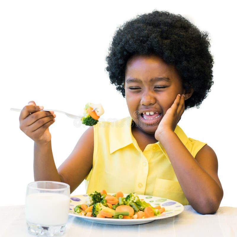 Enfant africain tirant le visage laid à la table de dîner photos libres de droits