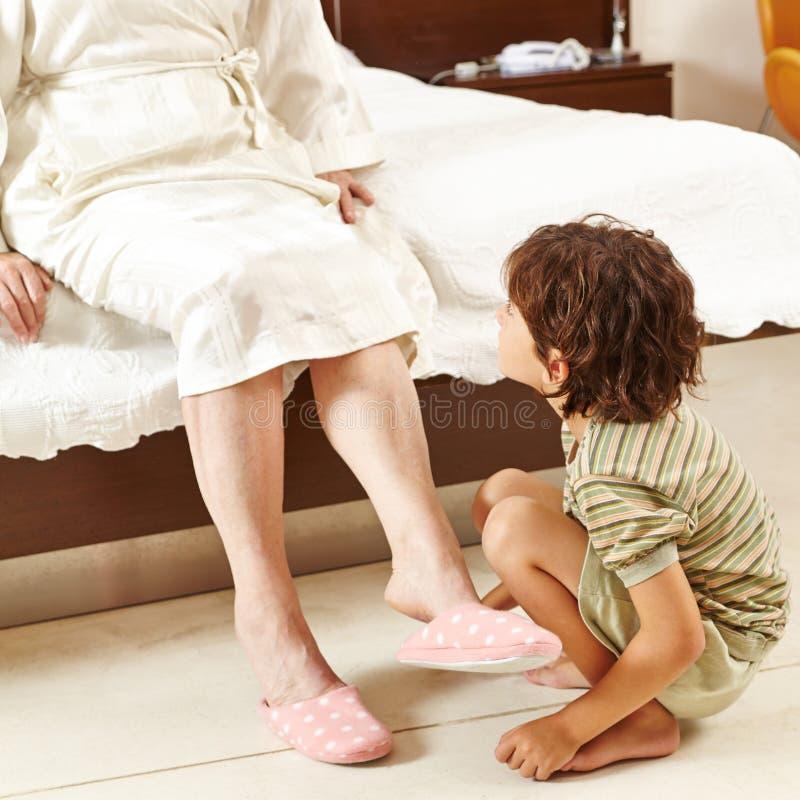 Enfant aidant la femme supérieure à la maison photos stock