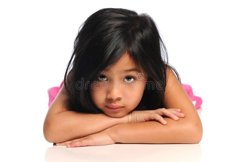 Enfant américain asiatique s'étendant sur l'étage images stock