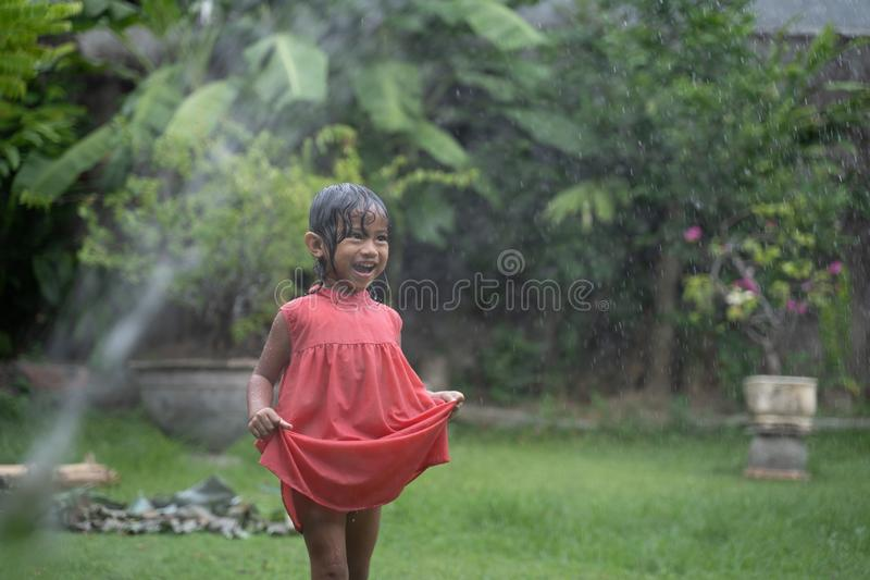 Enfant appréciant le jeu avec l'éclaboussure de l'eau dans le jardin photo libre de droits