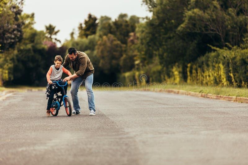 Enfant apprenant à monter une bicyclette images libres de droits