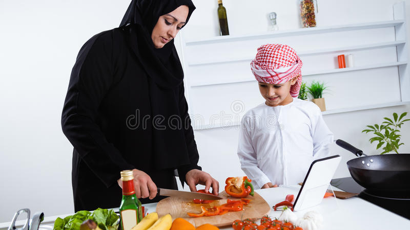 Enfant arabe dans la cuisine avec sa mère photo libre de droits