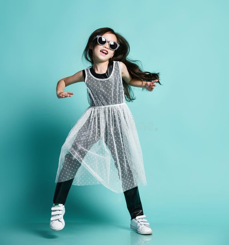 Enfant asiatique élégant gai de bébé dans les vêtements noirs et blancs modernes et les danses de lunettes de soleil aux sauts de images stock