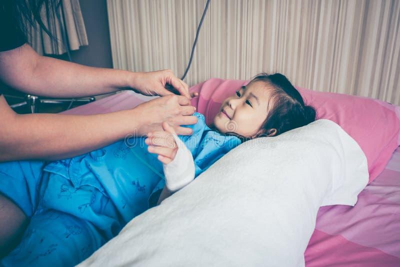 Enfant asiatique admis dans l'hôpital avec l'égouttement intraveineux salin dessus photographie stock