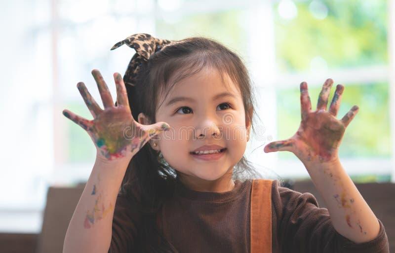 Enfant asiatique avec la main peinte sale dans la salle de classe d'art photo stock