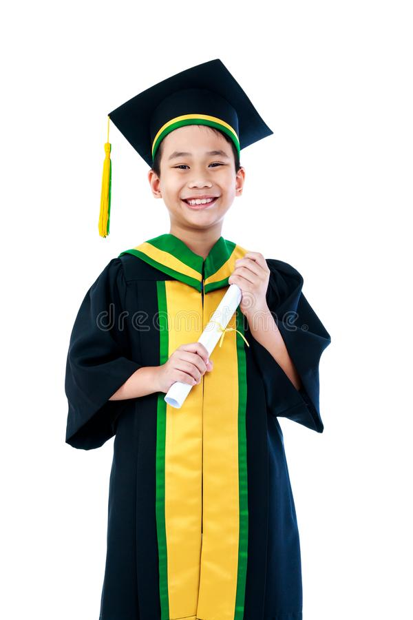 Enfant asiatique dans la robe d'obtention du diplôme avec le sourire de certificat de diplôme images libres de droits