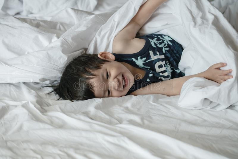 Enfant asiatique de plan rapproché sur le lit avec le mouvement d'amusement pendant le matin image stock