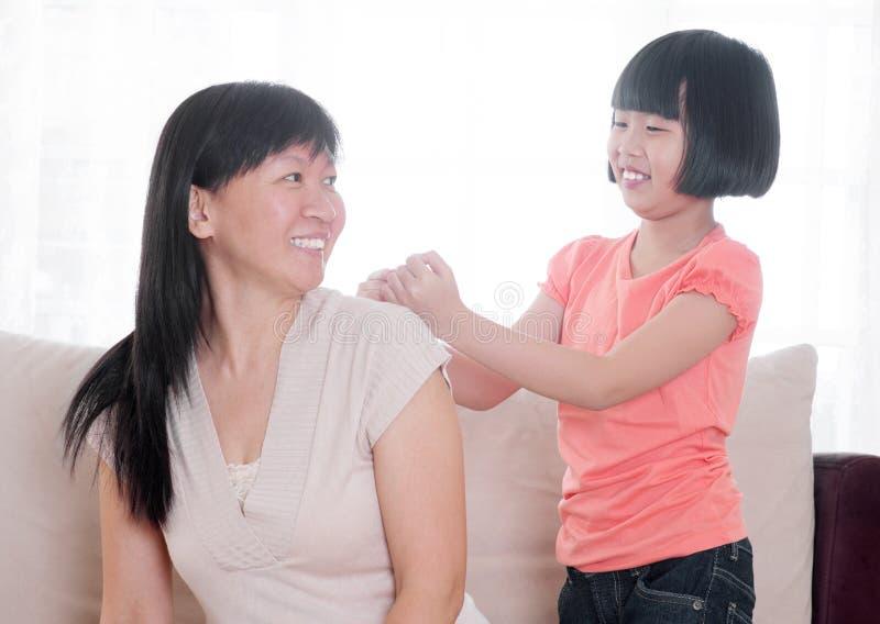 Enfant asiatique faisant le massage d'épaule à sa mère photo libre de droits