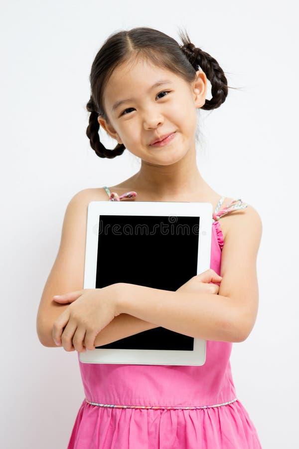 Enfant asiatique heureux avec la tablette photos stock
