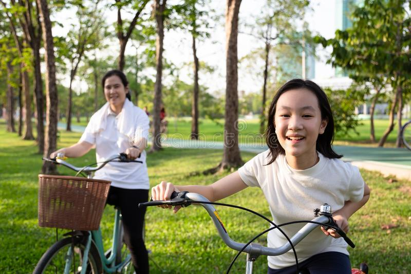 Enfant asiatique heureux de petite fille avec la bicyclette en parc extérieur, fille de sourire avec la mère sur un tour de vélo  image libre de droits