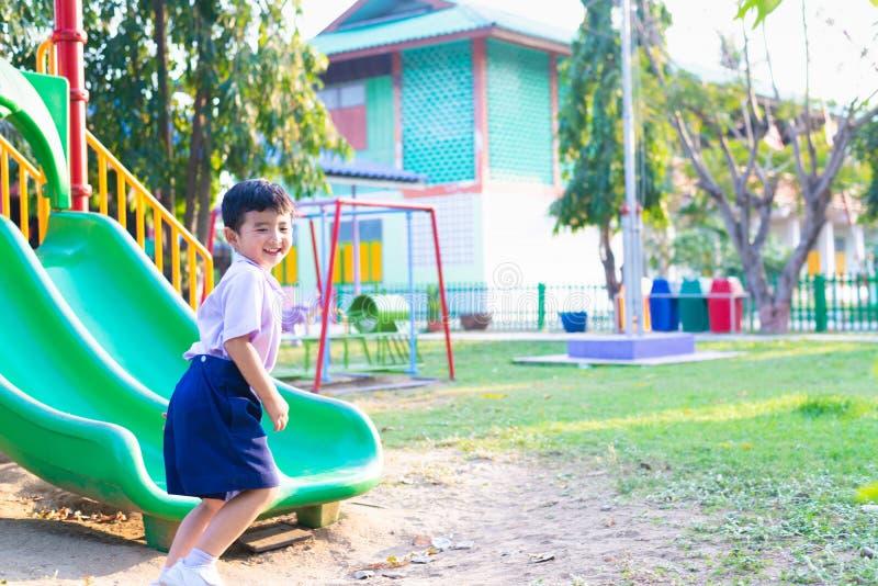 Enfant asiatique jouant la glissi?re au terrain de jeu sous la lumi?re du soleil en ?t?, enfant heureux dans le jardin d'enfants images stock
