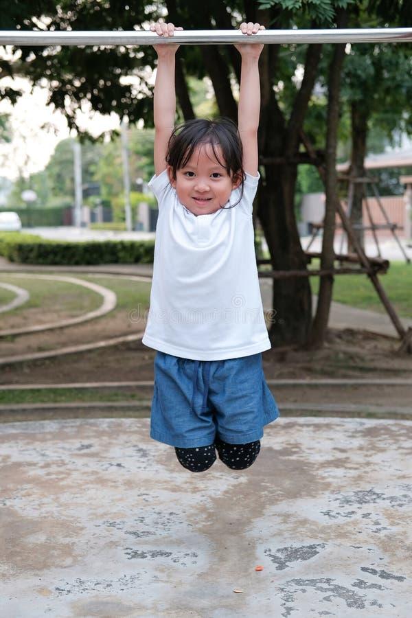 Enfant asiatique mignon accroché au bar attenant à l'aire de jeux du parc du village Activités sportives en plein air pour les en photographie stock libre de droits