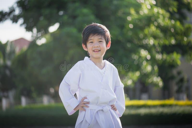 Enfant asiatique mignon dans le kimono blanc pendant le karaté de formation image stock