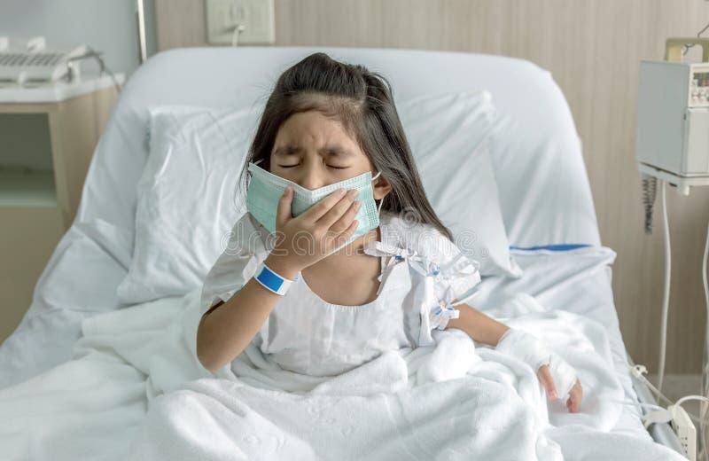 Enfant asiatique patient toussant avec le masque sur l'hôpital images stock