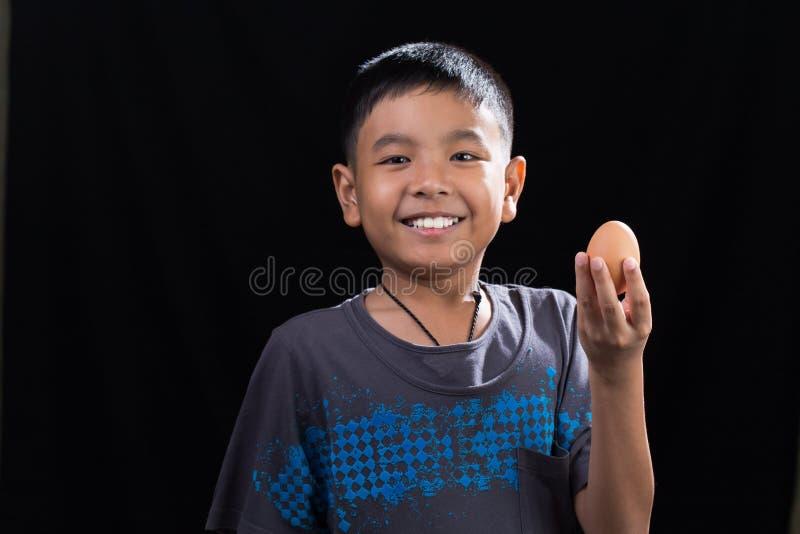 Enfant asiatique tenant l'oeuf dans sa main sur le fond noir photographie stock