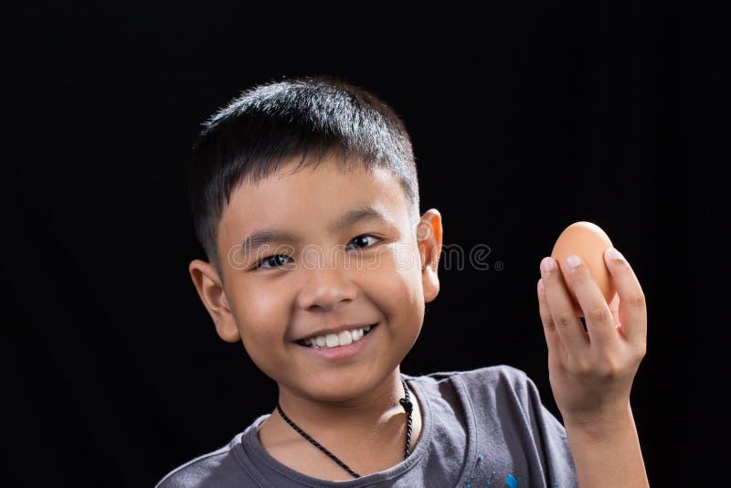 Enfant asiatique tenant l'oeuf dans sa main sur le fond noir photos libres de droits