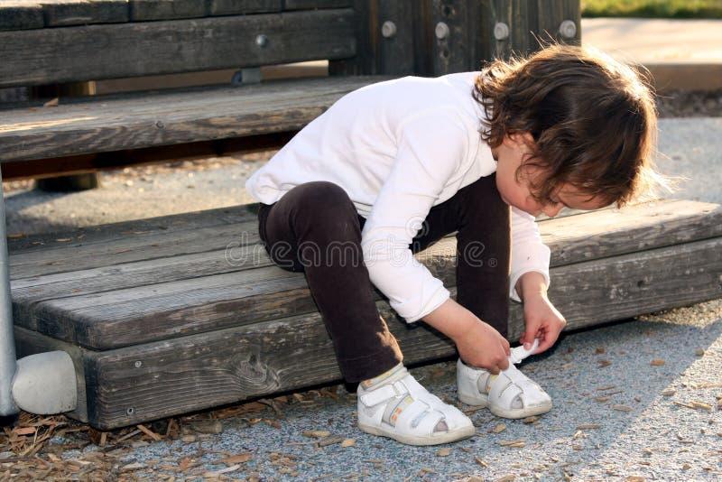 Enfant attachant sa chaussure photographie stock