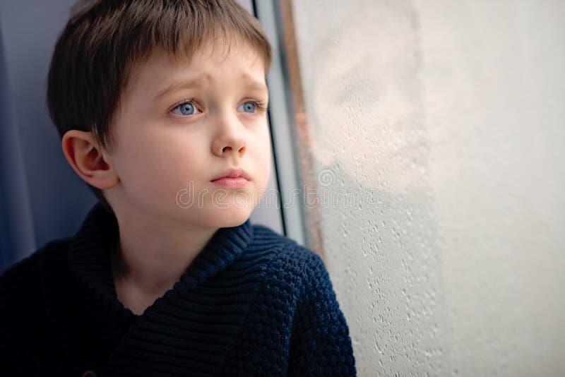 Enfant attendant par la fenêtre pleuvoir d'arrêt photos stock