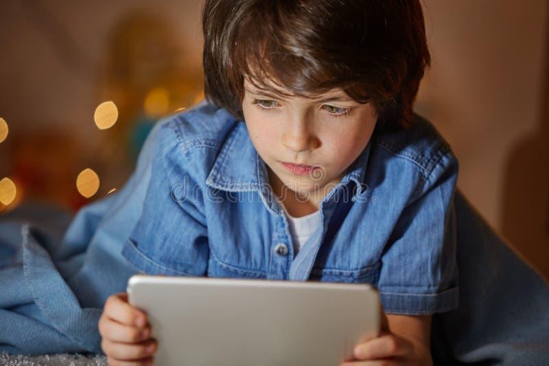 Enfant attentif surfant dans l'Internet avec le presse-papiers photos libres de droits
