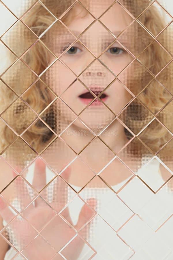 Enfant autiste brouillé derrière le carreau images stock