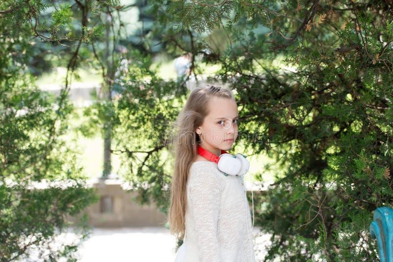 Enfant avec de longs cheveux blonds en parc d'été Jeu de petite fille sur l'air frais extérieur Enfant de mode avec des écouteurs image libre de droits