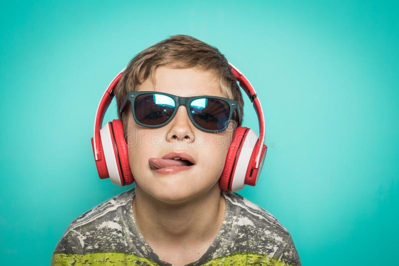 Enfant avec des écouteurs de la musique et de l'expression drôle photographie stock