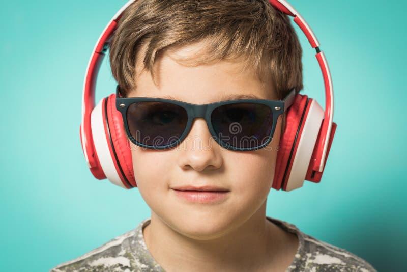 Enfant avec des écouteurs de la musique et de l'expression drôle photographie stock libre de droits