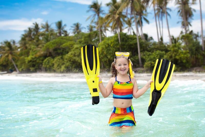 Enfant avec des ailerons de bain naviguant au schnorchel sur la plage tropicale image stock