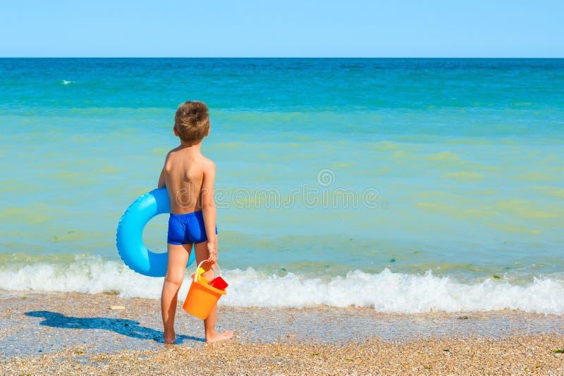 Enfant avec des jouets, regardant la mer photos libres de droits