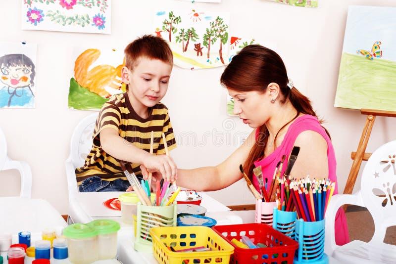 Enfant avec des peintures d'attraction de professeur dans la chambre de pièce. photographie stock