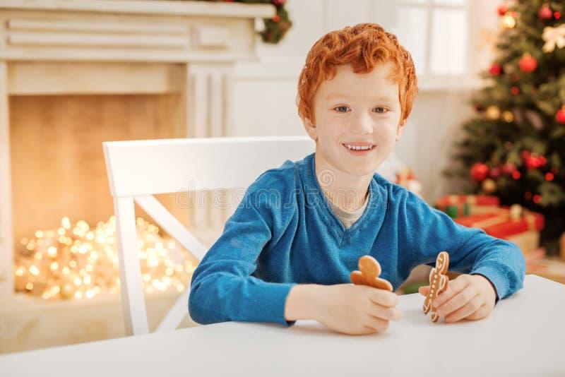 Enfant avec du charme de gingembre souriant tout en jouant avec des bonhommes en pain d'épice photo stock