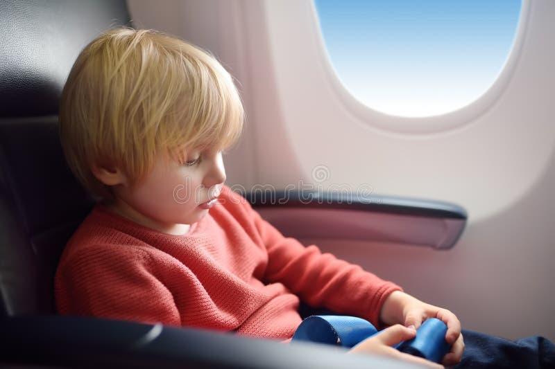 Enfant avec du charme voyageant en un avion Petit gar?on s'asseyant par la fen?tre d'avions pendant le vol Transports aériens ave photographie stock libre de droits