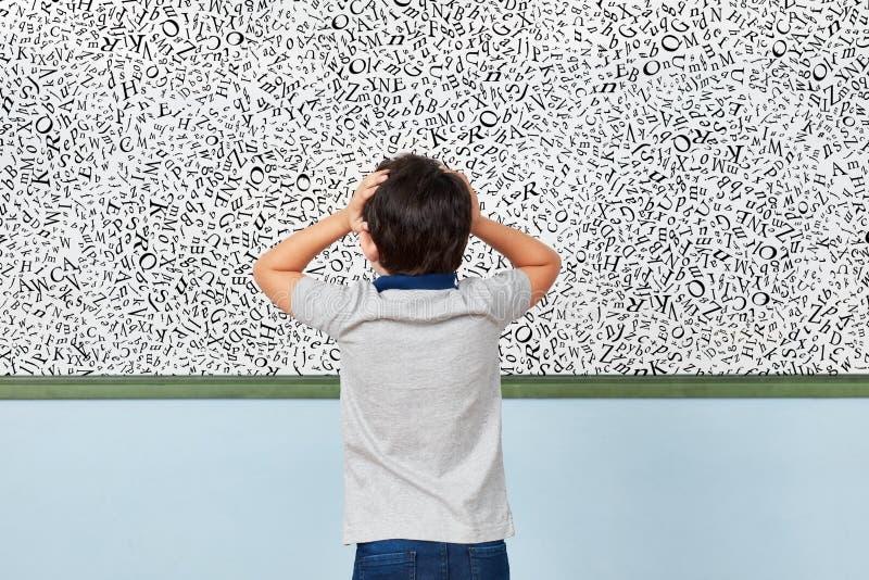 Enfant avec la dyslexie devant le tableau blanc dans l'école primaire photographie stock libre de droits